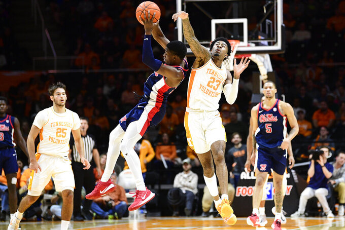 Tennessee guard Jordan Bowden (23) and Mississippi guard Bryce Williams (14) college while chasing the ball during an NCAA college basketball game at Thompson-Boling Arena in Knoxville, Tenn. on Tuesday, Jan. 21, 2020. (Calvin Mattheis/Knoxville News Sentinel via AP)
