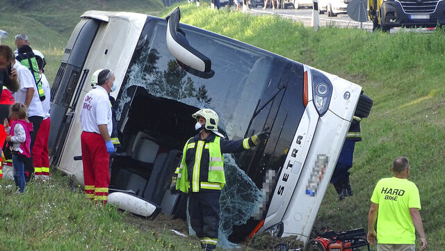 Ambulances and firefighters stand next to a bus after the vehicle went off the road and overturned in a ditch at the 115-meter section of the M5 motorway leading to Budapest, in Kiskunfelegyhaza, Hungary, Sunday, Aug. 9, 2020. One person is known to have died in the accident and others are reported injured aboard the tourist bus travelling from Poland to Hungary. (Ferenc Donka/MTI via AP)