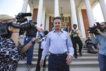 FILE - In this Sept. 27, 2017, file photo, Louisville men's basketball coach Rick Pitino leaves Grawemeyer Hall after having a meeting with the university's interim president Greg Postel, in Louisville. Ky. The University of Louisville Athletic Association and Rick Pitino have agreed to settle a federal lawsuit, with the former Cardinals men's basketball coach's changing his termination to a resignation. The settlement unanimously approved Wednesday, Sept. 18, 2019, by the ULAA states that Pitino has received compensation and the school agrees not to pursue further legal action. (Michael Clevenger/The Courier-Journal via AP, File)