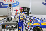 Chase Elliott stands by his trophy in victory lane after winning a NASCAR Cup Series auto race at Charlotte Motor Speedway in Concord, N.C., Sunday, Oct. 11, 2020. (AP Photo/Nell Redmond)