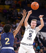 Utah State guard Sam Merrill (5) passes the ball as Montana State forward Quentin Guliford (2) defends during an NCAA college basketball game Tuesday, Nov. 5, 2019, in Logan, Utah. (Eli Lucero/The Herald Journal via AP)