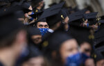 An engineering graduate of the Universite Libre De Bruxelles, looks from between mortarboards during a graduation ceremony at the Grand Place in Brussels, Wednesday, Sept. 30, 2020. Many of these students were supposed to graduate in June, but with exams cancelled and COVID-19 regulations in place many students were unable to manage that in time. Pandemic restrictions limited the guest invitations to only 2 persons for each graduate. (AP Photo/Virginia Mayo)
