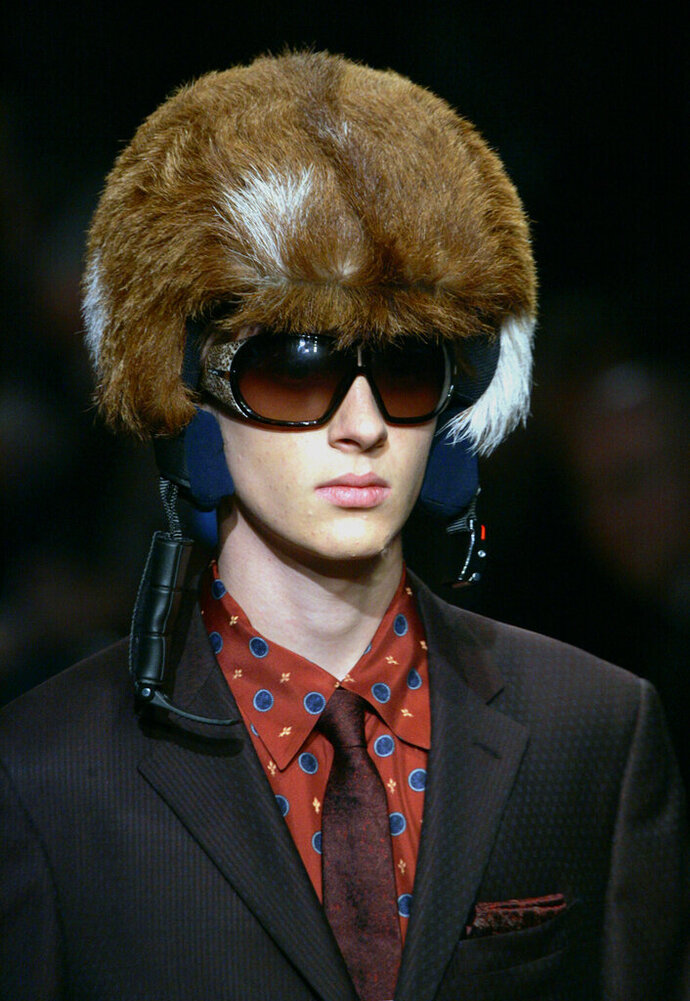 FILE - In this  Monday, Jan. 16, 2006 file photo, a model shows off a furred helmet, during the Prada Fall/Winter 2006/2007 men's fashion collection, presented in Milan, Italy. The Prada Group has become the latest luxury fashion house to go fur-free. Prada said Wednesday, May 22, 2019 that it will no longer include animal fur in its designs and new products from the spring-summer 2020 women's collection, which will be previewed next September. (AP Photo/Luca Bruno, File)
