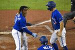 Toronto Blue Jays' Vladimir Guerrero Jr., left, and Randal Grichuk, right, celebrate after scoring against the New York Yankees on a double by Alejandro Kirk during the sixth inning of a baseball game in Buffalo, N.Y., Thursday, Sept. 24, 2020. (AP Photo/Adrian Kraus)