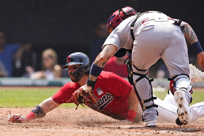 Cleveland Indians' Austin Hedges scores as St. Louis Cardinals' Yadier Molina is late on the tag in the fourth inning of a baseball game, Wednesday, July 28, 2021, in Cleveland. (AP Photo/Tony Dejak)