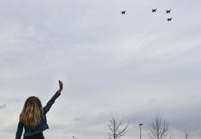 Michela Blosfield waves to members of the Colorado Air National Guard's 140th Wing as the F-16 Fighting Falcon jets fly over UCHealth Memorial North Hospital in Colorado Springs, Colo., Wednesday, May 6, 2020, to salute local health care workers, first responders and essential workers. (Chancey Bush/The Gazette via AP)