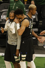 Milwaukee Bucks forward Giannis Antetokounmpo, front right, speaks to Khris Middleton at the end of Game 6 of a second-round NBA basketball playoff series against the Brooklyn Nets, Thursday, June 17, 2021, in Milwaukee. (AP Photo/Jeffrey Phelps)