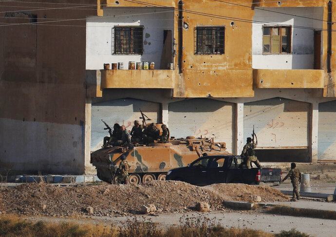 In this photo taken from the Turkish side of the border between Turkey and Syria, in Akcakale, Sanliurfa province, southeastern Turkey, Turkish-backed Syrian opposition fighters advance with theirs armoured personnel carrier in Tel Abyad, Syria, Sunday, Oct. 13, 2019. Fighting continued into the afternoon in Tel Abyad, where smoke could be seen rising from several points in the town. (AP Photo/Lefteris Pitarakis)