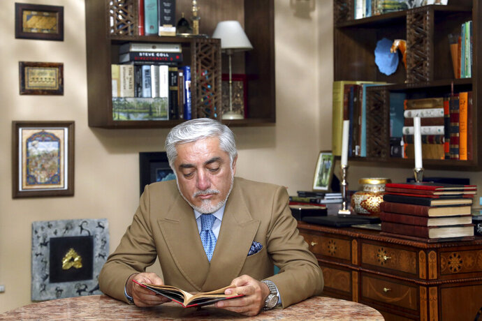 Abdullah Abdullah, a candidate in Afghanistan's upcoming presidential election looks at a book after an interview at his house in Kabul, Afghanistan, Thursday, Sept. 26, 2019. Abdullah, a leading contender in this weekend's Afghan presidential election, is alleging widespread abuses of power by his rival, incumbent President Ashraf Ghani. (AP Photo/Ebrahim Noroozi)