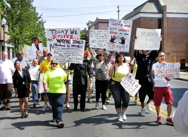 FILE - In this Friday, June 12, 2015, file photo, demonstrators carry signs in Martinsburg, W.Va., as they protest the killing of Winchester, Va., resident Wayne Jones by Martinsburg police on March 13, 2013. The city of Martinsburg has agreed to settle an excessive force lawsuit filed by the family of Jones, a homeless Black man, who was shot 22 times by police.  (Onofrio Castiglia/The Winchester Star via AP, File)