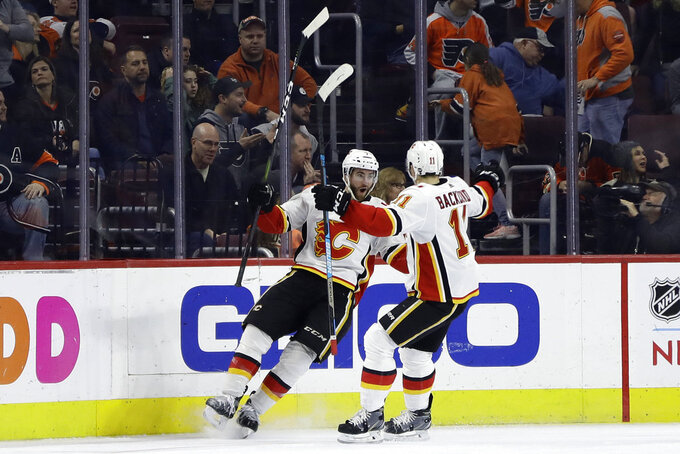 Calgary Flames' TJ Brodie, left, celebrates with Mikael Backlund after Brodie scored the game-winning goal in overtime of an NHL hockey game against the Philadelphia Flyers, Saturday, Jan. 5, 2019, in Philadelphia. Calgary won 3-2. (AP Photo/Matt Slocum)