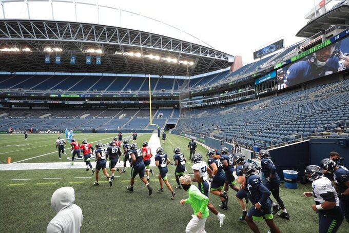 FILE - The Seattle Seahawks take to an empty CenturyLink Field for the NFL football team's scrimmage Saturday, Aug. 22, 2020, in Seattle. One of the best home field advantages in the NFL will sit empty on Sunday night, Sept. 20. The Seahawks know it will be strange having no fans inside CenturyLink Field. But being an opponent in Seattle has gained such a reputation even some Patriots are disappointed there won't be fans. (Bettina Hansen/The Seattle Times via AP, File)
