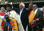 Democratic presidential candidate U.S. Sen. Bernie Sanders is escorted by Comanche Nation Chairman William Nelson, right, and other Native American leaders into Comanche Nation Arena for the annual Comanche Nation Fair Powwow, Sunday, Sept. 22, 2019, in Lawton, Okla. (AP Photo/Gerardo Bello)