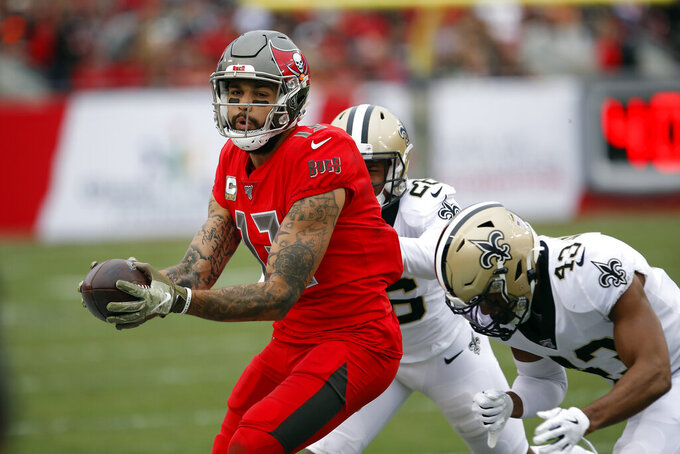 Tampa Bay Buccaneers wide receiver Mike Evans (13) makes a catch in front of New Orleans Saints cornerback P.J. Williams (26) and free safety Marcus Williams (43) during the second half of an NFL football game Sunday, Nov. 17, 2019, in Tampa, Fla. (AP Photo/Mark LoMoglio)