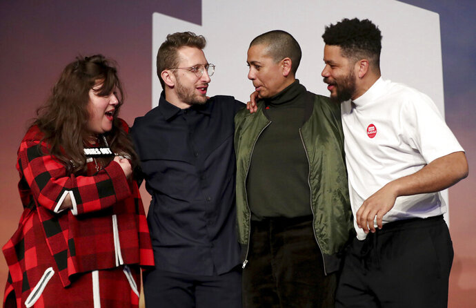 From left; Tai Shani, Lawrence Abu Hamdan, Helen Cammock and Oscar Murillo, after being announced as the winners for the 2019 Turner Prize at Dreamland Margate, in London, Tuesday December 3, 2019. All four of the artists chosen as finalists won this year's award after they wrote to the jury and asked to be treated as a collective, prize organizers said Tuesday. (Gareth Fuller/PA via AP)