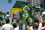 People hold Brazilian flags during a protest against President Jair Bolsonaro, demanding his resignation for mishandling the pandemic, corruption over vaccine contracts and a faltering economy, at Paulista Avenue, Sao Paulo, Brazil, Sunday, Sep. 12, 2021. (AP Photo/Marcelo Chello)