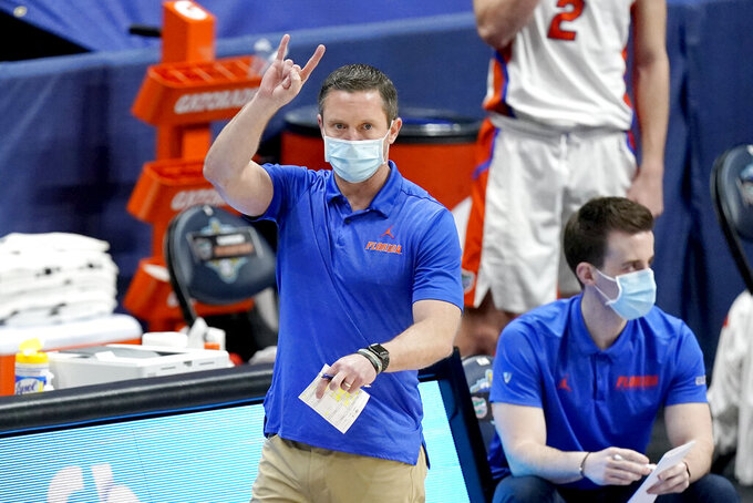 Florida head coach Mike White directs his players in the first half of an NCAA college basketball game against Vanderbilt in the Southeastern Conference Tournament Thursday, March 11, 2021, in Nashville, Tenn. (AP Photo/Mark Humphrey)
