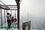 Tourists take a picture at Skybox of Kuala Lumpur Tower as city stands shrouded with haze in Kuala Lumpur, Malaysia, Friday, Sept. 13, 2019. Malaysian authorities plan to conduct cloud-seeding activities to induce rain to ease the haze. The government said it will press Jakarta to take immediate action to put out the burning forests and ensure the fires won't occur again. (AP Photo/Vincent Thian)