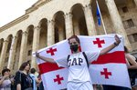 An opposition demonstrator holds a Georgian national flag at a rally in front of the Georgian Parliament building in Tbilisi, Georgia, Monday, June 24, 2019. Demonstrators have returned to parliament for daily rallies, demanding the release of detained protesters, the ouster of the nation's interior minister and changes in the electoral law to have legislators chosen fully proportionally rather than the current mix of party-list and single-mandate representatives. (AP Photo/Shakh Aivazov)