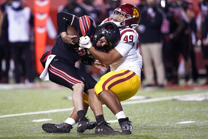 Southern California defensive lineman Tuli Tuipulotu (49) sacks Utah quarterback Jake Bentley (8) in the second half during an NCAA college football game Saturday, Nov. 21, 2020, in Salt Lake City. (AP Photo/Rick Bowmer)