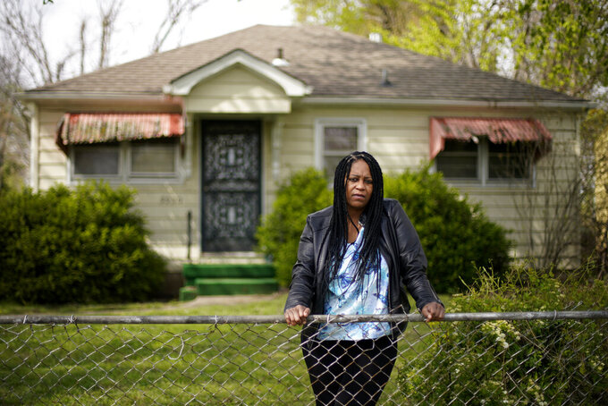 Karen Pitchford-Knox stands in front of her home Monday, April 19, 2021, in Kansas City, Kan. Pitchford-Knox found out from a state senator that her home was put up for sale by Wyandotte County in January when she fell behind on her property tax payments after loosing her job during the pandemic. (AP Photo/Charlie Riedel)