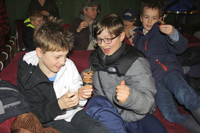 In this Saturday, Jan. 18, 2020 photo, from left, Orrin Noon, 10, Arlo Davis, 11, and Axel Boily, 10, beam at the crunchy critters they were about to eat at the Gold Town Theater in Juneau, Alaska. The boys were among the theatergoers who sampled edible insects prepared by David George Gordon. The bugs included seasoned chapulines, or Mexican grasshoppers, and cooked, farm-raised locusts, and the boys were ready to nosh on the crunchy critters. The reaction didn't surprise Gordon, a public speaker, naturalist and author known as the Bug Chef, who delivered a lecture before a screening of