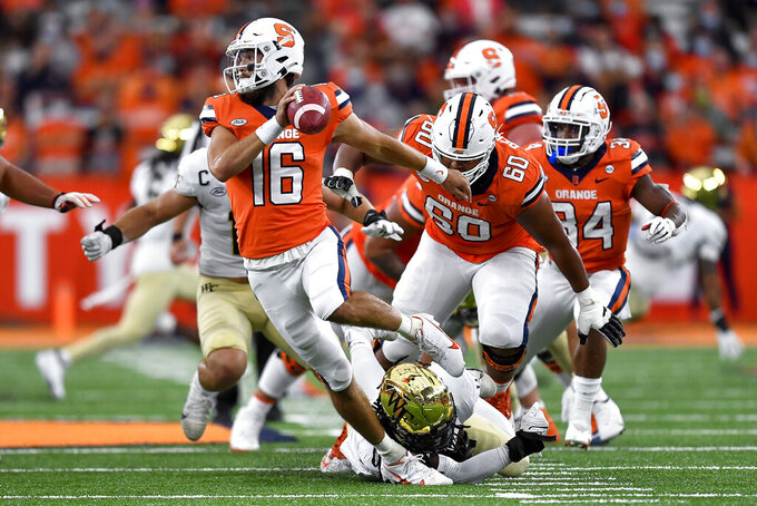 Syracuse quarterback Garrett Shrader (16) scrambles away from pressure by Wake Forest defensive lineman Luiji Vilain (2) during the first half of an NCAA college football game in Syracuse, N.Y., Saturday, Oct. 9, 2021. (AP Photo/Adrian Kraus)