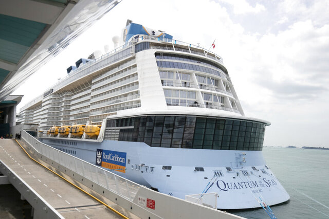 """The Quantum of the Seas cruise ship is docked at the Marina Bay Cruise Center Wednesday, Dec. 9, 2020 in Singapore. Royal Caribbean said in a statement that a guest on the Quantum of the Seas """"tested positive for coronavirus after checking in with our medical team."""