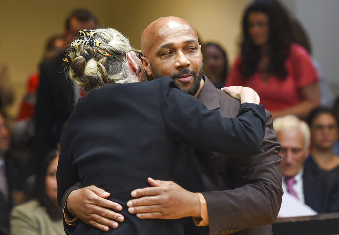 Keith Bush is embraced by his attorney, Adele Bernhard, Wednesday, May 22, 2019 at Suffolk County Courthouse in Riverhead, N.Y. after murder charges against him were vacated. Bush, who spent 33 years in prison for the 1975 murder of a high school classmate, had his conviction overturned Wednesday after a case review found Long Island prosecutors had long hid the fact that police looked at another possible suspect. (James Carbone/Newsday via AP, Pool)
