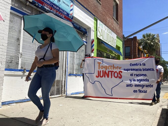 """Daisy Arvizu, left, participates in a street march in support of immigrant rights on Aug. 26, 2021, in El Paso, Texas, amid lingering concerns about gun violence targeting immigrants. She was at work inside a Walmart in El Paso in August 2019 when a gunman opened fire in a shooting that killed 23 people, spurring her husband, Martin Portillo, to later to buy a handgun for their protection. A new """"constitutional carry"""" law in Texas allows most gun owners age 21 and older to carry a holstered handgun — concealed or not — in public without getting a license and related training. (AP Photo/Morgan Lee)"""
