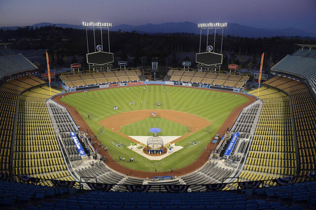 FILE - In Oct. 10, 2018, file photo, Dodger Stadium is seen after sunset in Los Angeles. Dodger Stadium will serve as a vote center for the presidential election in November 2020, making the Dodgers the first Major League Baseball team to make their venue available for voting. (AP Photo/Mark J. Terrill, File)