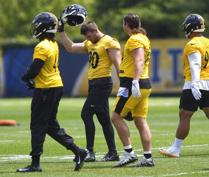 Pittsburgh Steelers linebacker T.J. Watt (90) takes off his helmet during a break at the NFL football team's training camp in Pittsburgh on Friday, July 23, 2021. (Steve Mellon/Pittsburgh Post-Gazette via AP)