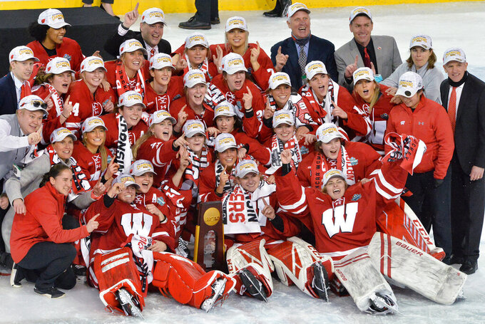 Wisconsin teammates celebrate their NCAA college Women's Frozen Four hockey tournament championship win over Northeastern, Saturday, March 20, 2021, at Erie Insurance Arena in Erie, Pa. (Greg Wohlford/Erie Times-News via AP)