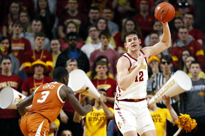 Iowa State forward Michael Jacobson catches a pass over Texas guard Courtney Ramey, left, during the second half of an NCAA college basketball game, Saturday, Feb. 15, 2020, in Ames, Iowa. (AP Photo/Charlie Neibergall)