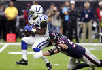Indianapolis Colts running back Marlon Mack (25) is hit by Houston Texans defensive end J.J. Watt (99) on a run during the first half of an NFL wild card playoff football game, Saturday, Jan. 5, 2019, in Houston. (AP Photo/Michael Wyke)