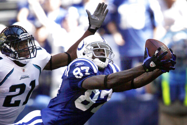 FILE - In this Sept. 13, 2009, file photo, Indianapolis Colts wide receiver Reggie Wayne, right, reaches out while attempting a catch under the defense of Jacksonville Jaguars cornerback Derek Cox in the second half of an NFL football game in Indianapolis. Safety Troy Polamalu, wide receiver Reggie Wayne and linebacker Patrick Willis are first-year eligible players among the 25 semifinalists of the modern era for the Pro Football Hall of Fame announced Tuesday, Nov. 26, 2019. (AP Photo/AJ Mast, File)
