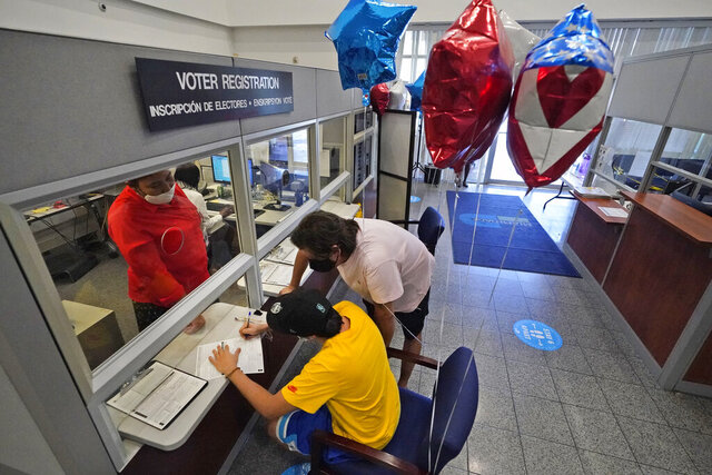 Lucas Saez, foreground, 22, fills out his voter registration form as his father Ramiro Saez, center rear, looks on, Tuesday, Oct. 6, 2020, at the Miami-Dade County Elections Department in Doral, Fla. Florida Gov. Ron DeSantis extended the state's voter registration deadline after heavy traffic crashed the state's online system and potentially prevented thousands of enrolling to cast ballots in next month's presidential election. Saez attempted to register to vote six times the night before without any luck. (AP Photo/Wilfredo Lee)