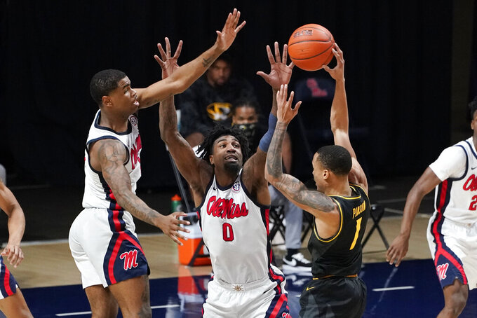 Mississippi forward Romello White (0) and guard Luis Rodriguez (15) defend against Missouri guard Xavier Pinson (1) during the second half of an NCAA college basketball game in Oxford, Miss., Wednesday, Feb. 10, 2021. (AP Photo/Rogelio V. Solis)