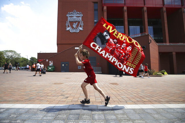 Liverpool fan Dillon Parry waves a flag outside Anfield in Liverpool, England, Friday June 26, 2020. Liverpool clinched its first league title since 1990 on Thursday, ending an agonizing title drought. (Martin Rickett/PA via AP)
