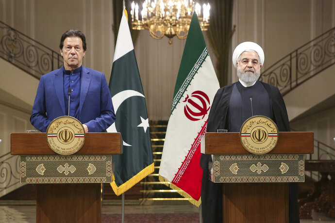 In this photo released by the official website of the office of the Iranian Presidency, Iranian President Hassan Rouhani, right, and Pakistani Prime Minister Imran Khan give a joint press conference at the Saadabad Palace, in Tehran, Iran, Sunday, Oct. 13, 2019. (Office of the Iranian Presidency via AP)