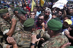 Hezbollah supporters scuffle with Lebanese army soldiers while protesting the visit to Lebanon by Gen. Frank McKenzie, the head of US Central Command, outside the Rafik Hariri International Airport in Beirut, Lebanon, Wednesday, July 8, 2020. The Arabic placard that reads,