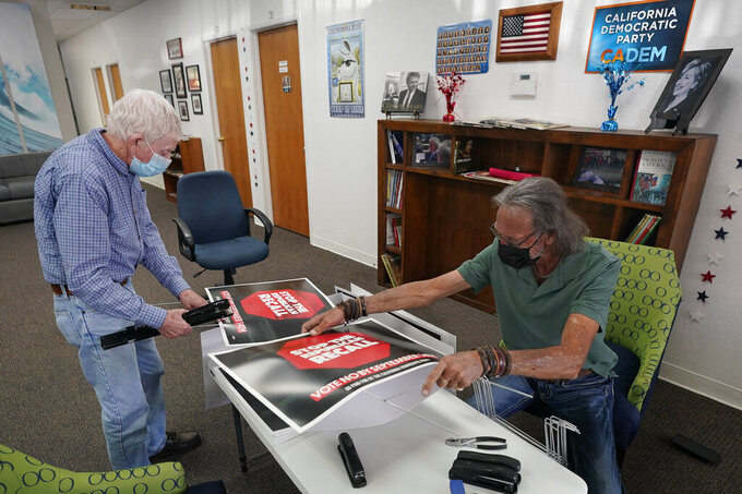 Volunteer Merle Canfield, left, and Brian Babbitt, operations director for the Fresno County Democratic Party, assemble yard signs against the Sept. 14, recall election of Gov. Gavin Newsom, at party headquarters in Fresno, Calif., Thursday, July 29, 2021. While Democratic registration almost doubles that of Republicans in the state, Democratic Party leaders fear Republicans appear more eager to vote. (AP Photo/Rich Pedroncelli)