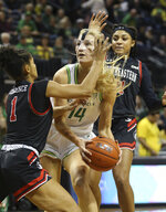 Oregon's Lydia Giomi, center, works for position under the basket against Northeastern's Kendall Currence, left, and Samantha Michel, right, the third quarter of an NCAA college basketball game in Eugene, Ore., Monday, Nov. 11, 2019. (AP Photo/Chris Pietsch)