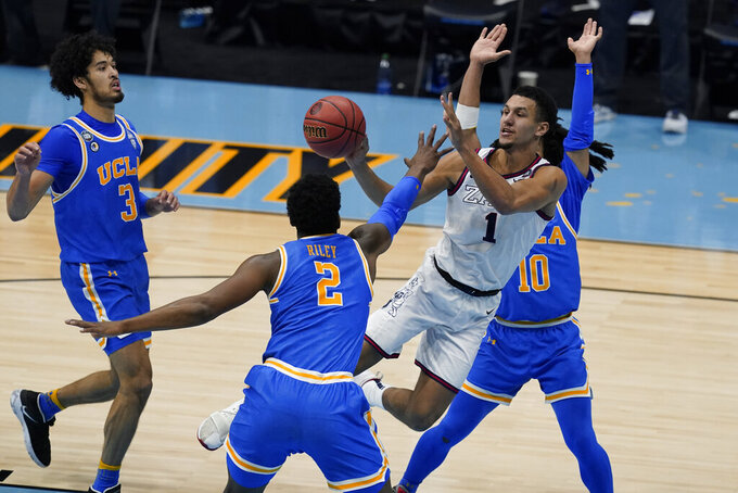 Gonzaga guard Jalen Suggs (1) passes between UCLA guard Johnny Juzang (3), forward Cody Riley (2) and guard Tyger Campbell (10) during the first half of a men's Final Four NCAA college basketball tournament semifinal game, Saturday, April 3, 2021, at Lucas Oil Stadium in Indianapolis. (AP Photo/Darron Cummings)
