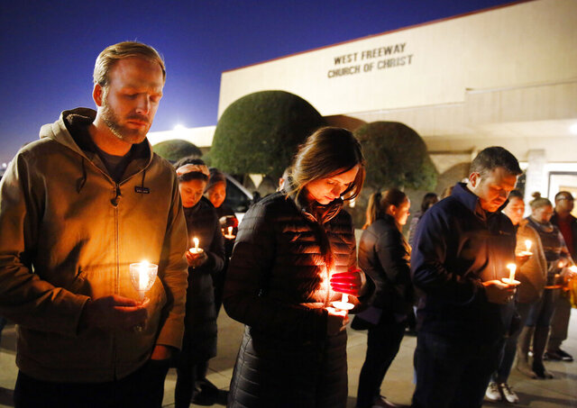 FILE - In this Monday, Dec. 30, 2019, file photo, church and community members, including Matt Pacholczyk, left, and his wife, Faith Pacholczyk, stand outside West Freeway Church of Christ for a candlelight vigil in White Settlement, Texas. The machete attack on a rabbi's home in Monsey, New York, during Hanukkah and the shooting of worshippers at a Texas church are refocusing attention on how vulnerable worshippers are during religious services. FBI hate crime statistics show there is reason for concern. (Tom Fox/The Dallas Morning News via AP, File)
