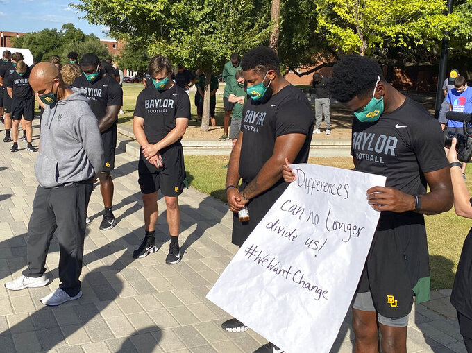 Members of the Baylor football team including Dave Aranda, left, bow their heads during a prayer after marching around campus, Thursday, Aug. 27, 2020, in Waco, Texas, protesting the shooting of Jacob Blake in Wisconsin. (Rod Aydelotte/Waco Tribune-Herald via AP)
