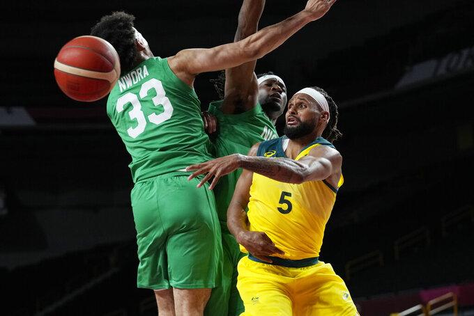 Australia's Patty Mills (5) passes the ball around Nigeria's Jordan Nwora (33) during a men's basketball preliminary round game at the 2020 Summer Olympics, Sunday, July 25, 2021, in Saitama, Japan. (AP Photo/Eric Gay)