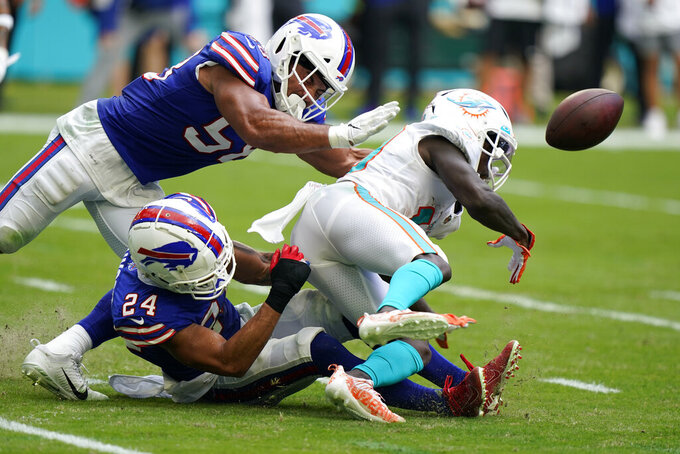 Miami Dolphins wide receiver Jakeem Grant (19) fumbles the ball as he is tackled by Buffalo Bills cornerback Taron Johnson (24), bottom, and Buffalo Bills outside linebacker Matt Milano (58) during the first half of an NFL football game, Sunday, Sept. 19, 2021, in Miami Gardens, Fla. (AP Photo/Wilfredo Lee)