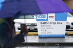 A pedestrian walks past a King County ballot drop box, closed until ballots are mailed about three weeks before the election, on a Seattle street Thursday, Sept. 24, 2020. (AP Photo/Elaine Thompson)