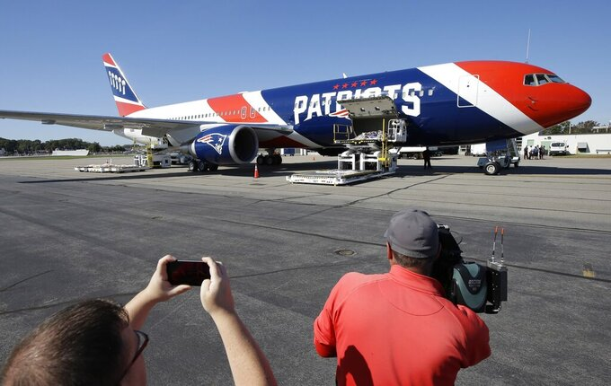 FILE - In this Oct. 4, 2017, file photo, the New England Patriots customized Boeing 767 jet rests on the tarmac at T.F. Green Airport, in Warwick, R.I. The Patriots private team plane is expected to land in Boston on Thursday, April 2, 2020, returning from China with more than one million masks to help control the spread of the coronavirus. The new coronavirus causes mild or moderate symptoms for most people, but for some, especially older adults and people with existing health problems, it can cause more severe illness or death. (AP Photo/Steven Senne, File)